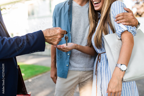 Young happy couple talking with real estate agent and buying a new house Canvas Print