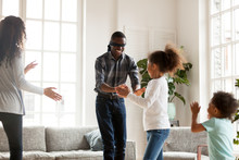 Happy African Family With Little Preschool Adorable Son And Daughter Spending Free Time Together On Weekend At New Modern Home. Playful Blind Daddy With Covered Eyes Play Hide And Seek In Living Room