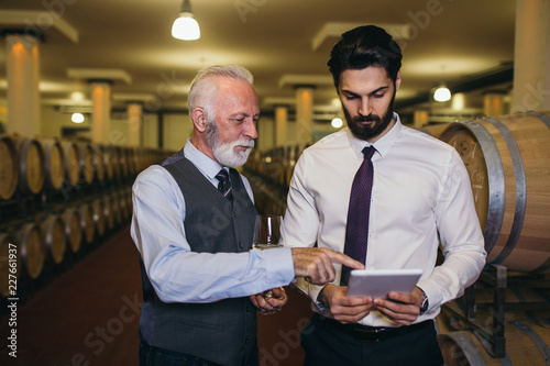 Foto Winemakers in wine cellar holding glass of wine and checking it