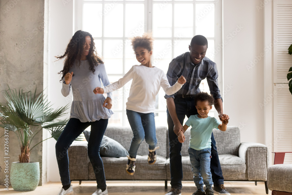 Fototapety, obrazy: Full length black African whole family have a fun. Married couple with little kids toddler son preschool daughter dancing moving in living room at new home. Happy family spend time together concept