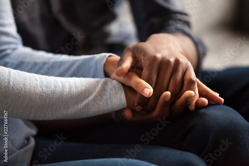 Fotografía Close up black woman and man in love sitting on couch two people holding hands
