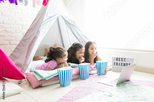 Female Friends Enjoying Snacks While Watching Laptop In Tent Canvas