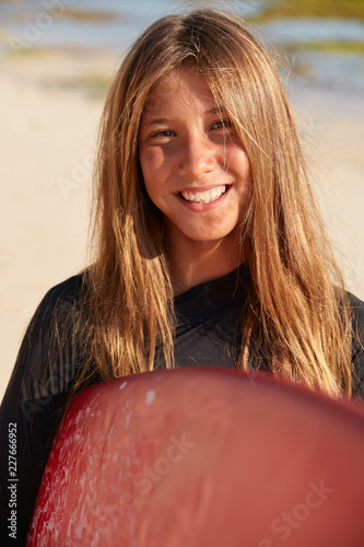Photo Close up shot of talented young female surfboarder likes windsurfing, carries bo