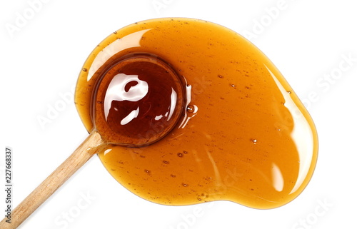 Honey and wooden spoon isolated on white background, top view