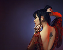 Amazing Dark-haired Sexy Tender Graceful Princess Of Japan, A Young Girl In A Light Red Dress With An Open Back And A Lotus Tattoo With A Precious Stone. Art Processing Photo With Blue Background