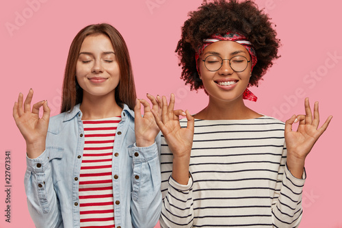 Pleased two women of different race make okay gesture with both hands, close eyes, try to concentrate, enjoy pleasure, wears striped clothes, isolated over pink background. Body language concept