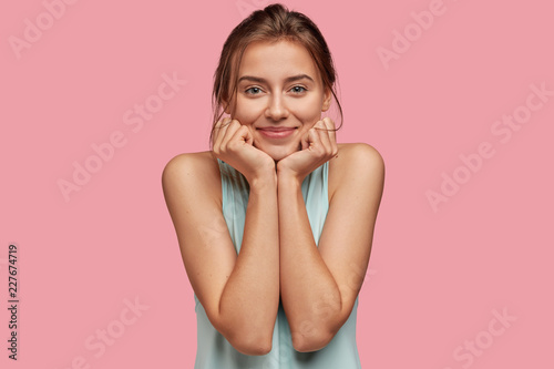 Fotografija  Satisfied woman with delighted expression, keeps hand under chin, has healthy skin, green eyes, dark hair, wears casual clothes, isolated over pink background