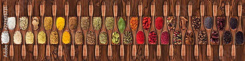 Obraz Spices and herbs from different countries in wooden spoons. Colorful seasonings on   table background, top view. - fototapety do salonu