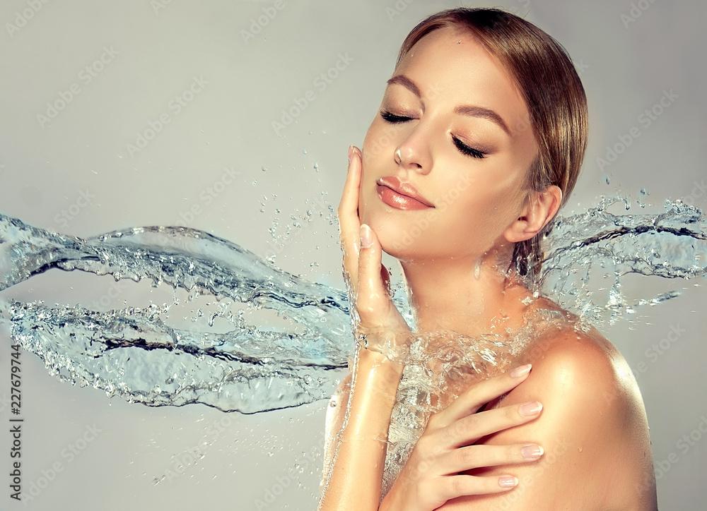 Fototapeta Beautiful spa woman with water splashes. Moisturizing facial skin, beauty and care.