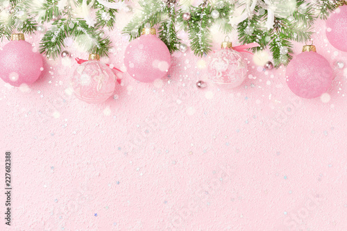 christmas border of new years ornaments fir and snow on pastel pink winter holidays