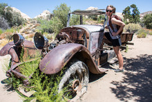 Cute Woman Hiker Poses By An Abandoned Old Fashioned Car Rusting And Decaying In The Desert Of Joshua Tree National Park