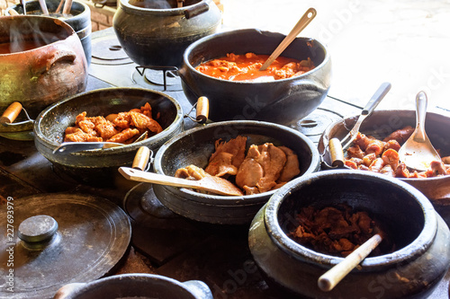 Traditional Brazilian food being prepared in clay pots and in the old and popular wood stove