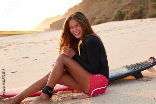Fotografía  Happy professional female surfer wears boardshorts, has positive smile, slender legs, legrope around ankle, has sustainable sunscreen on cheeks, enjoys summer time