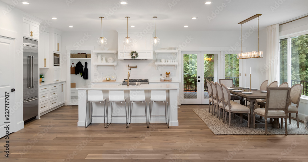 Fototapeta Beautiful kitchen and dining room panorama in new luxury home, with pendant lights, dining room table and chairs, kitchen island, and counters