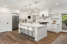 Beautiful Kitchen In New Luxury Home With Island, Pendant Lights, Hardwood Floors, And Stainless Steel Appliances