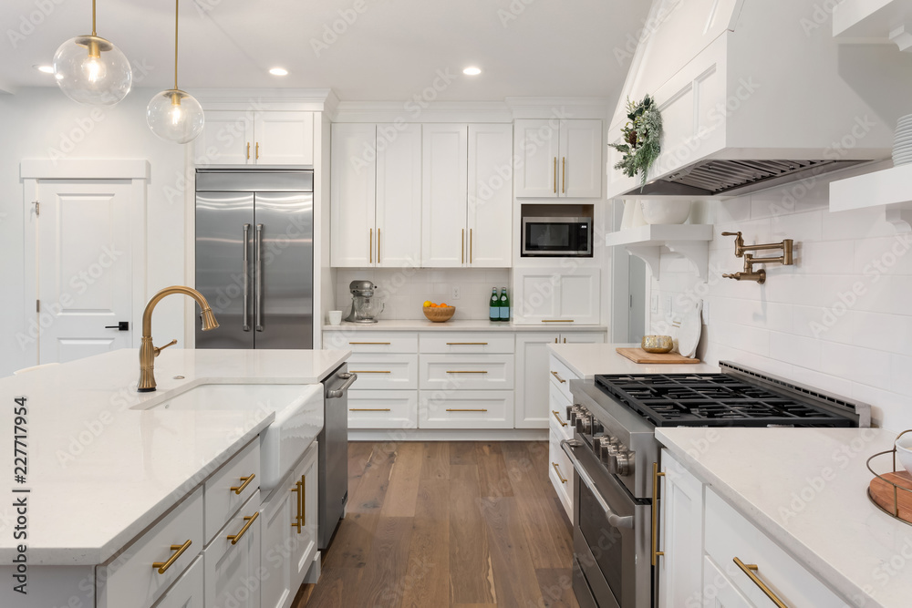 Fototapety, obrazy: Beautiful kitchen detail in new luxury home. Features island, pendant lights, hardwood floors, and stainless steel appliances