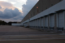 A Empty Loading Dock At Sunset, Soon It Will Be Filled With Trucks And Trailers Delivering The Freight From Around The World.lights Just Coming On And There's Clouds In The Background