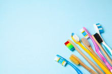 Many Colored Toothbrushes On Blue Background. How To Choose Toothbrush