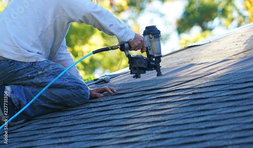 Obraz na płótnie handyman using nail gun to install shingle to repair roof
