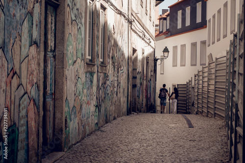 Spoed Foto op Canvas Smal steegje lovely couple walking in narrow street with graffiti