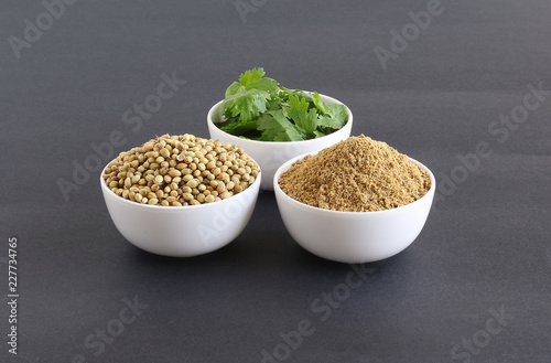 Coriander powder with coriander seeds and leaves, which are healthy food, in bowls.