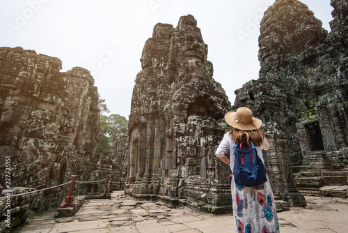 Fototapeta premium Młoda podróżniczka odwiedzająca świątynię Bayon w kompleksie Angkor Wat, dziedzictwo architektury khmerskiej w Siem Reap w Kambodży