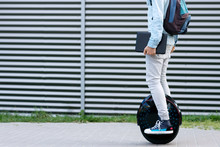 Modern Young Adult Male Businessman Student Freelancer With Backpack And Laptop Riding On Ecological Electric Transport Futuristic Eco Electric Unicycle Scooter, Balancing Electric Wheel. Eco Planet.