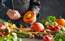 Chef In Black Scooping Seeds Out Of Small Pumpkin