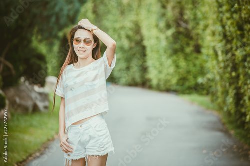 Valokuva  asian thin hipster girl wearing sunglasses walking in the green park relax holid