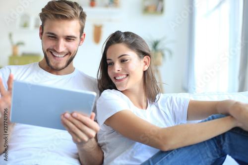Foto Young couple watching media content online in a tablet sitting on a sofa in the living room