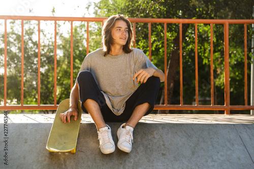 Valokuvatapetti Photo of european skater boy 16-18 in casual wear sitting on ramp with skateboar