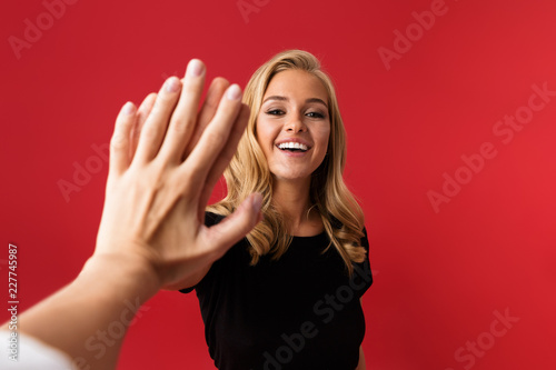 Excited woman looking camera give a high five to someone's hand isolated over red background Poster Mural XXL