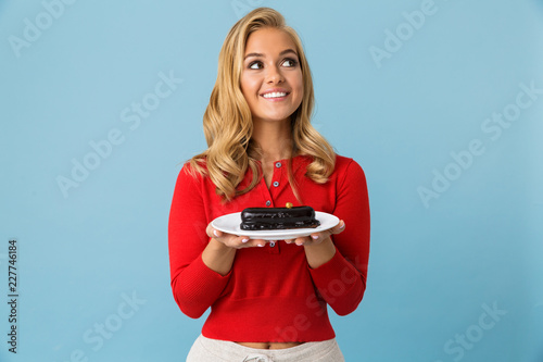 Photographie  Portrait of happy woman 20s wearing red shirt holding plate with eclair cake, is