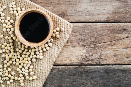 black light soy sauce in wooden bowl with soy bean on gunny sack cloth, top view, copy space