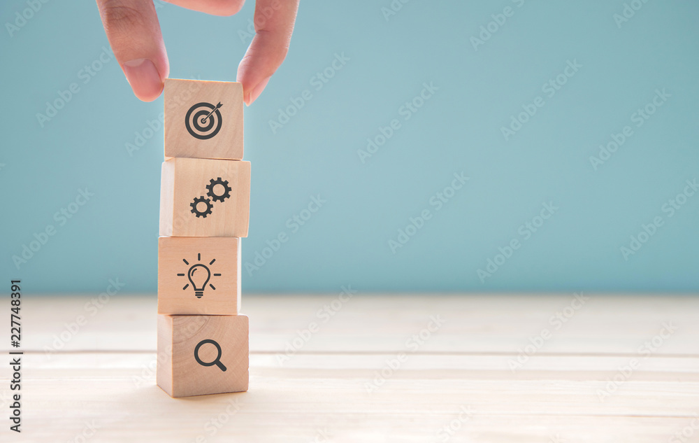 Fototapeta Businessman hand arranging wood block with icon business strategy and Action plan, copy space.