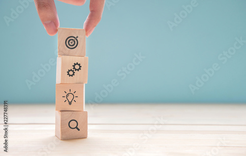 Vászonkép  Businessman hand arranging wood block with icon business strategy and Action plan, copy space