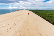 Woman walking on large sand dune