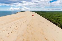 Woman Walking On Large Sand Dune