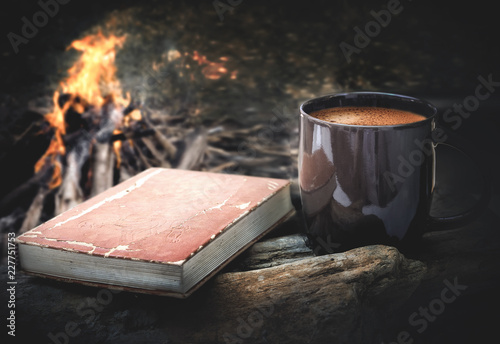cup of coffee and book with campfire night background.