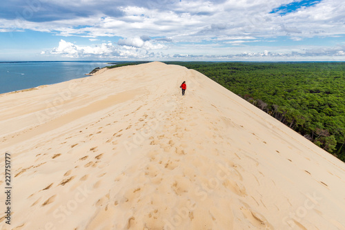 Photo Woman walking on large sand dune