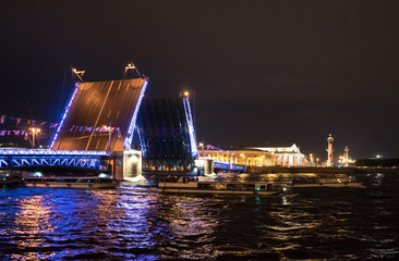 Fototapeta na wymiar Divorced Palace Bridge, the Spit of Vasilyevsky Island and boats under the bridge at night in St. Petersburg. Russia