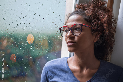 Foto  Lonely black woman near window thinking about something