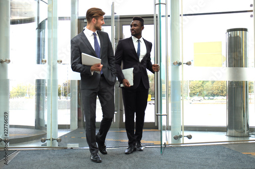 Two multinational young businessmen entering in office building with glass doors Fototapeta