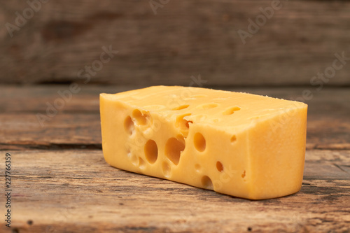 Piece of maasdam cheese on wooden background. Yellow cheese with holes on rustic wooden boards. Healthy milky product.