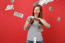 Crazy Woman In Striped Clothes Screaming Scattering Throwing Out Money Banknotes Lots Of Dollars Isolated On Bright Red Wall Background. People Sincere Emotions, Lifestyle Concept. Mock Up Copy Space.