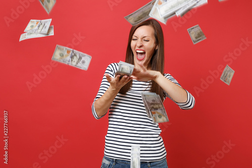 Cuadros en Lienzo Crazy woman in striped clothes screaming scattering throwing out money banknotes lots of dollars isolated on bright red wall background