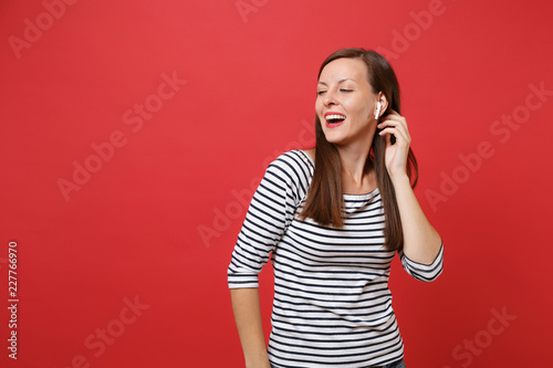 Fotografía  Portrait of stunning young girl in casual striped clothes with wireless earphones listening music isolated on bright red wall background