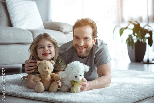 Friendly family. Portrait of happy man is embracing his little daughter with love. He is holding cute toy sheep near teddy bear in childish hands. They are lying on flooring and smiling