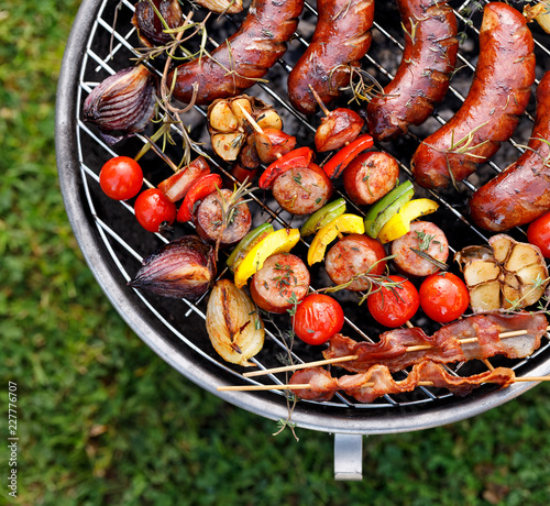 Grilled food. Various grilled products: Grilled sausages, meat and vegetable skewers, bacon and vegetables on the grill plate, outside. Barbecue, bbq