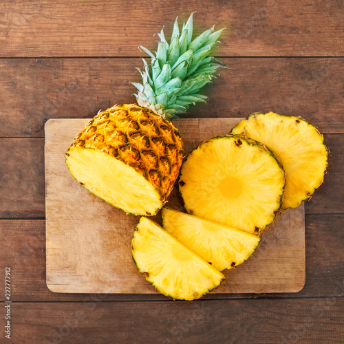 Pineapple on wood texture background. Whole and sliced tropical pineapple on wooden cutting board  with copy space. Top view.